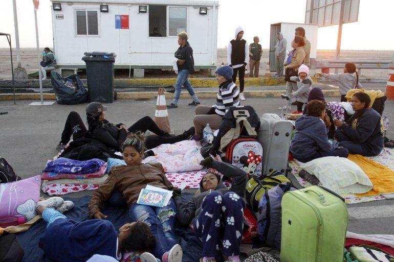Migrantes de Venezuela permanecen en el suelo a un puesto de control fronterizo en Chile