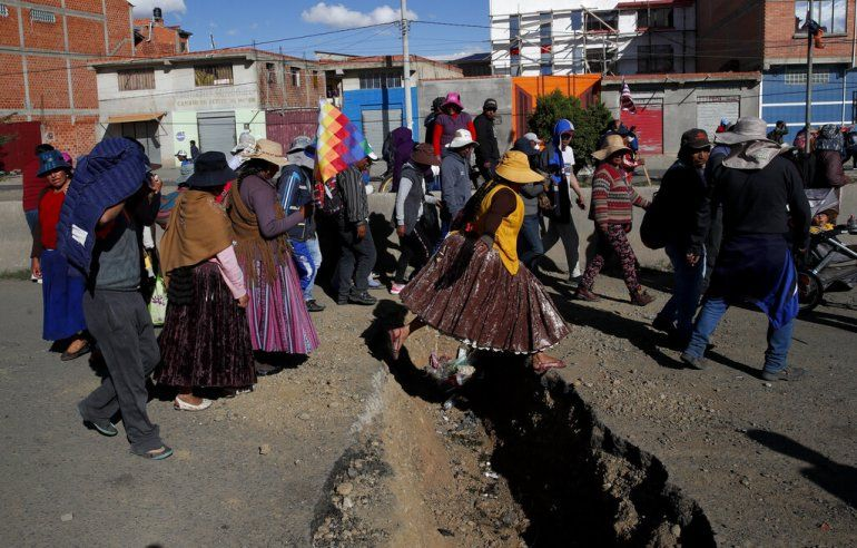 Los partidarios del expresidente Evo Morales pasan por una zanja excavada para evitar que los vehículos pasen por la carretera que conduce a la planta Yacimientos Petrolíferos Fiscales Bolivianos en El Alto