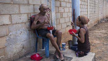 Haydé Chacín (der) y su esposo José Calderón comen algo donado por vecinos del barrio Los Hijos de Dios en Maracaibo, Venezuela, el 19 de noviembre del 2019. La anciana pareja sobrevive gracias a la caridad ajena.