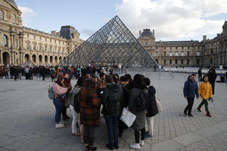 Turistas esperan y empleados en huelga se manifiestan en la entrada al Museo del Louvre