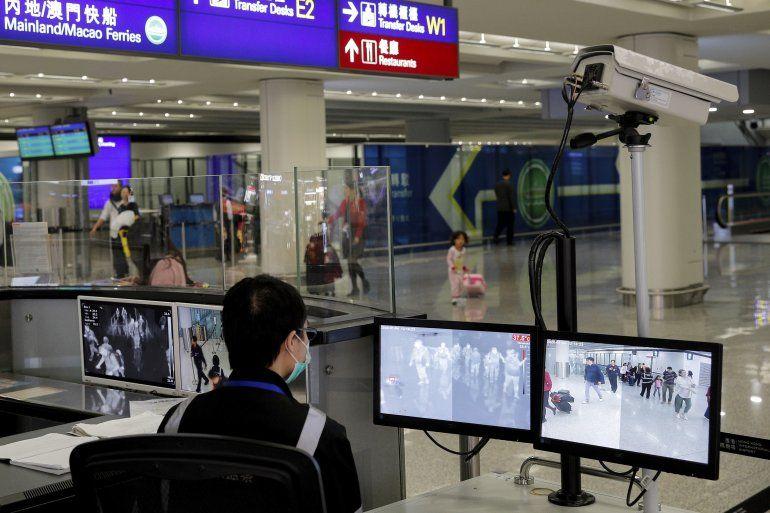 Fotografía de archivo del 4 de enero de 2020 de un agente de supervisión de salud mientras monitorea pasajeros que llegan al aeropuerto internacional de Hong Kong.