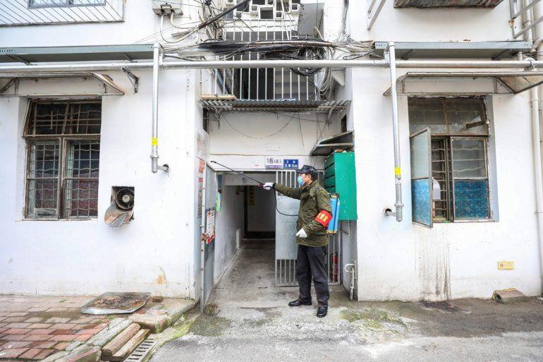 Un empleado del gobierno rocía desinfectante en un edificio residencial en Wuhan