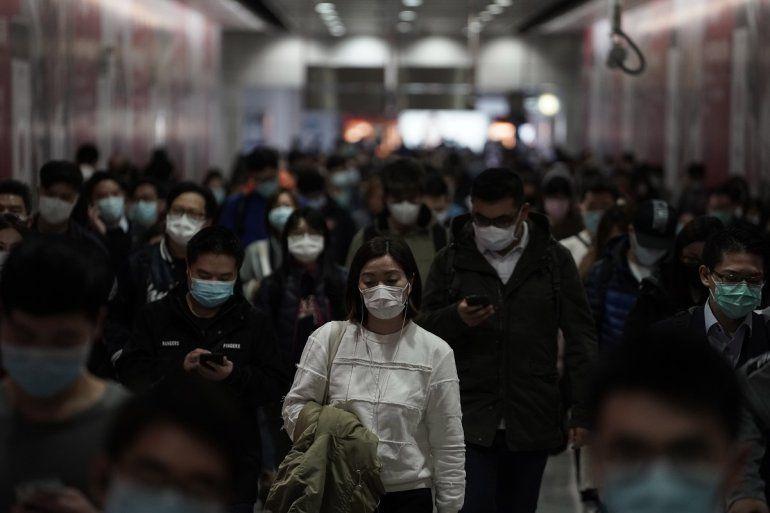 Personas con mascarillas caminan en una estación del tren subterráneo en Hong Kong