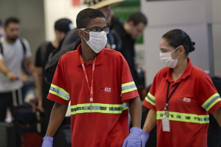 Los empleados del aeropuerto usan máscaras como precaución contra la propagación del nuevo coronavirus COVID-19 mientras trabajan en el Aeropuerto Internacional de Sao Paulo en Brasil
