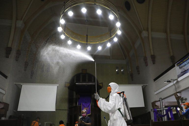 Un operario de la Agencia de Mitigación de Desastres rocía desinfectante dentro de una iglesia por temor a la expansión del nuevo coronavirus