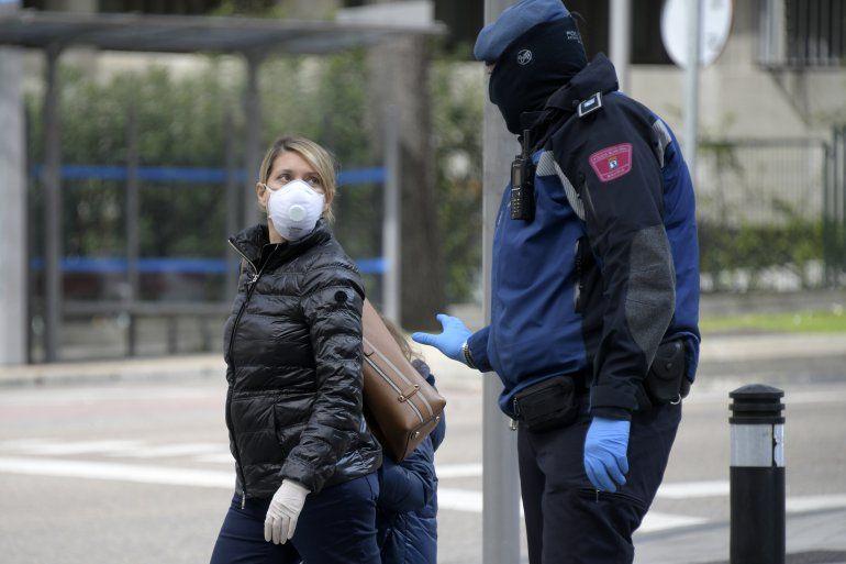 Un policía habla con una mujer y su niña en una desolada avenida en Madrid.
