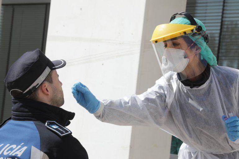 Una paramédico le realiza un examen del coronavirus a un policía en Madrid.