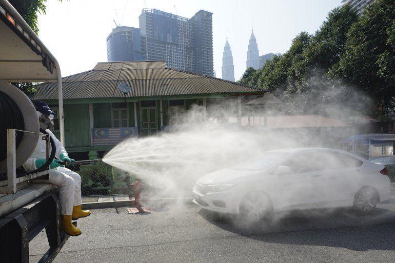 Personal sanitario rocía desinfectante sobre un barrio tradicional malasio en el centro de Kuala Lumpur