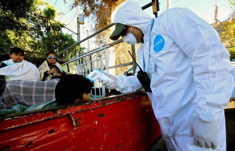 Un empleado de la Secretaría de Salud de México verifica la temperatura de un niño a bordo de un camión como medida preventiva contra la propagación del nuevo coronavirus