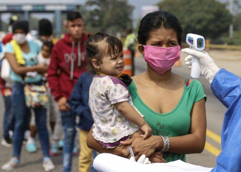 Empleados del Secretario de Salud toman la temperatura de los venezolanos que regresan al país desde Colombia