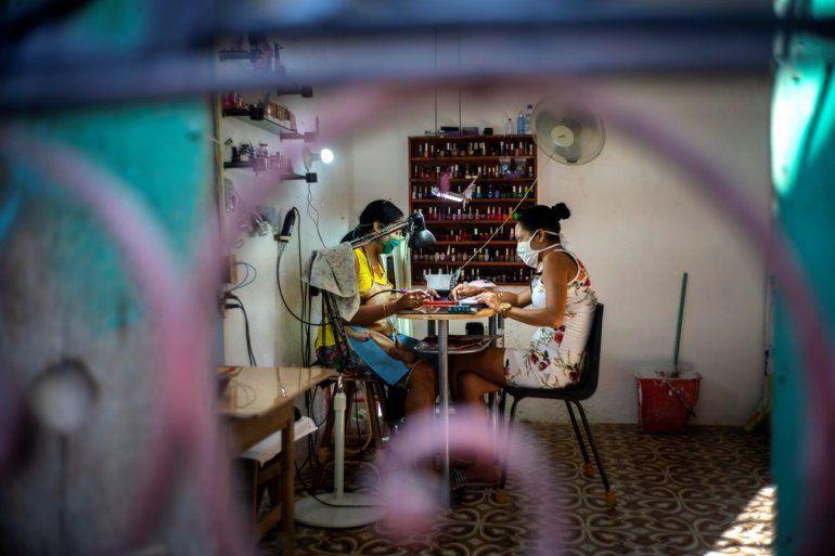 En esta imagen, tomada el 31 de marzo de 2020, dos mujeres, equipadas con mascarilla como medida de precaución contra el nuevo coronavirus, en un salón de manicura en una casa en La Habana, Cuba. Los negocios van en declive en Cuba tras la aparición del Covid-19.