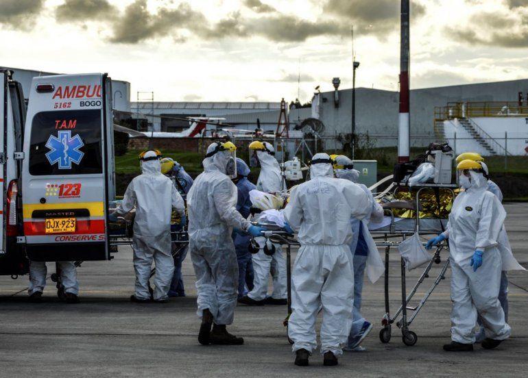 Trabajadores de la salud trasladan desde un avión a la ambulancia a personas heridas en una explosión. Un avión de la Fuerza Aérea de Colombia los transportó desde el norte de Colombia a Bogotá