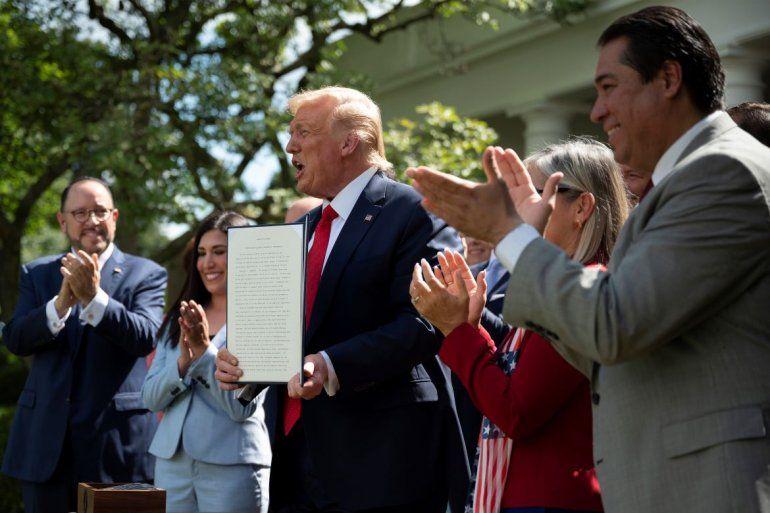 El presidente Donald Trump junto a destacados representantes de la comunidad hispana durante la firma de una orden ejecutiva que promueve el desarrollo económico y educativo de los hispanos, en la Rosaleda de la Casa Blanca, en Washington, el jueves 9 de julio de 2020.