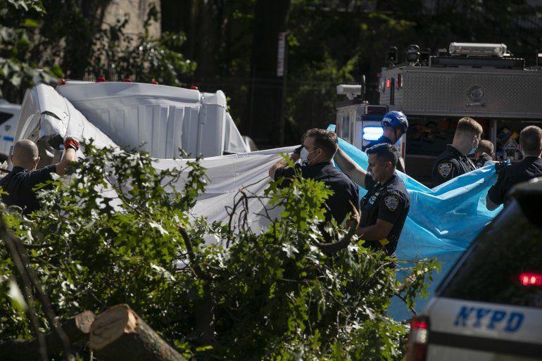 Policías de la ciudad de Nueva York tapan de la vista a una persona que murió después de que un árbol cayera sobre una camioneta cuando la tormenta tropical Isaías atravesaba Nueva York