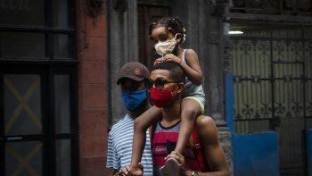 Personas con máscaras como precaución contra la propagación del nuevo coronavirus caminan en una calle de La Habana, Cuba, el 31 de agosto de 2020.