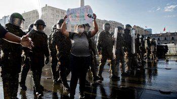 Un manifestante sostiene un cartel que dice Amnistía para los presos políticos junto a la policía antidisturbios durante una protesta contra el gobierno del presidente chileno Sebastián Piñera en Santiago, el 18 de noviembre de 2020.