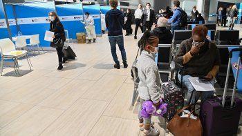 Los pasajeros que acaban de aterrizar desde Nueva York en un vuelo de Alitalia esperan para someterse a una prueba rápida de hisopado de antígeno para COVID-19.