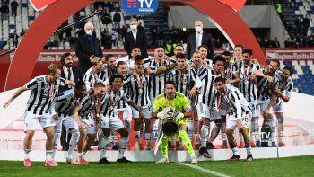 El portero italiano de la Juventus, Gianluigi Buffon, sostiene el trofeo del ganador mientras los jugadores de la Juventus celebran ganar la final del partido de fútbol de la Copa de Italia (Coppa Italia) Atalanta vs Juventus el 19 de mayo de 2021