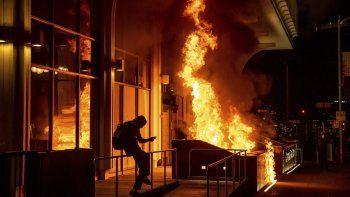 Manifestantes prenden fuego al frente del edificio de California Bank y Trust durante una protesta contra la brutalidad policial en Oakland, California, la noche del viernes 16 de abril de 2021.
