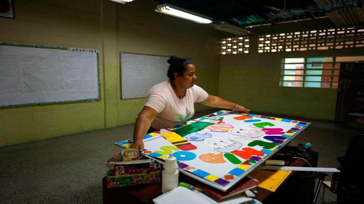 Una maestra lleva un cartel de bienvenida a un salón de clases de la escuela Jerman Ubaldo Lira en Caracas,.