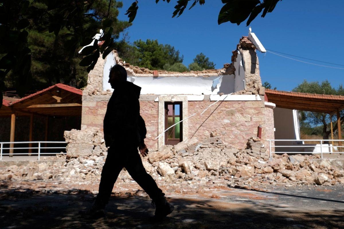 Un vecino pasa junto a una capilla ortodoxa griega dañada por un fuerte sismo en el poblado de Arcalochori, en la isla sureña de Creta, Grecia, el lunes 27 de septiembre de 2021