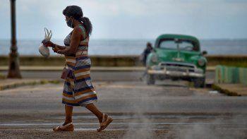 Una mujer que usa mascarilla como medida preventiva contra la pandemia del nuevo coronavirus COVID-19 camina en La Habana, el 20 de octubre de 2020.