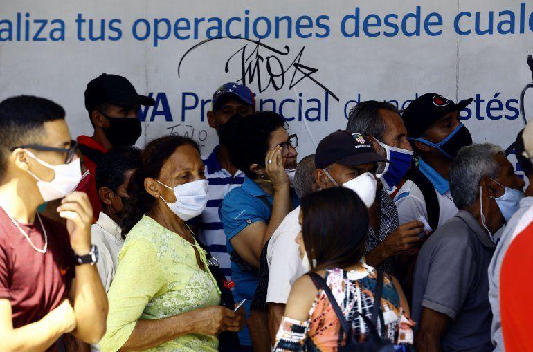 Personas esperan para ingresar a una agencia bancaria en Valencia