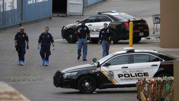 En imagen de archivo del martes 6 de agosto de 2019, un grupo de policías recorre la zona detrás de una tienda Walmart en el lugar de la masacre cerca de un centro comercial, en El Paso, Texas.