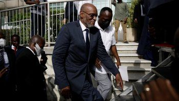 El nuevo primer ministro de Haití, Ariel Henry, sube escaleras acompañado de escoltas después de ser designado al cargo, el martes 20 de julio de 2021, en Puerto Príncipe