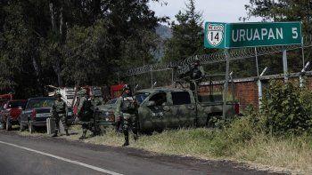 En esta fotografía del 6 de febrero de 2020, miembros de la Guardia Nacional mexicana vigilan una carretera con dirección a Uruapan, en el estado de Michoacán, México.