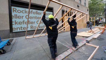 Unos trabajadores colocan una pared de madera el lunes 2 de noviembre de 2020 para proteger una tienda de LEGO en el Rockefeller Center, en la ciudad de Nueva York, previo al día de las elecciones presidenciales.