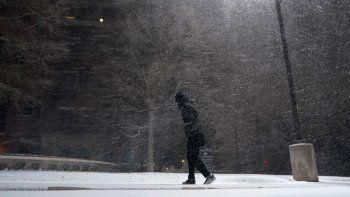 Una mujer camina bajo una nevada en San Anotnio, el domingo 14 de febrero de 2021. El hielo y la nieve cubrieron buena parte de Estados Unidos el domingo, provocando cancelaciones de vuelos, complicando los desplazamientos y llegando a zonas tan al sur como la costa texana del Golfo de México.