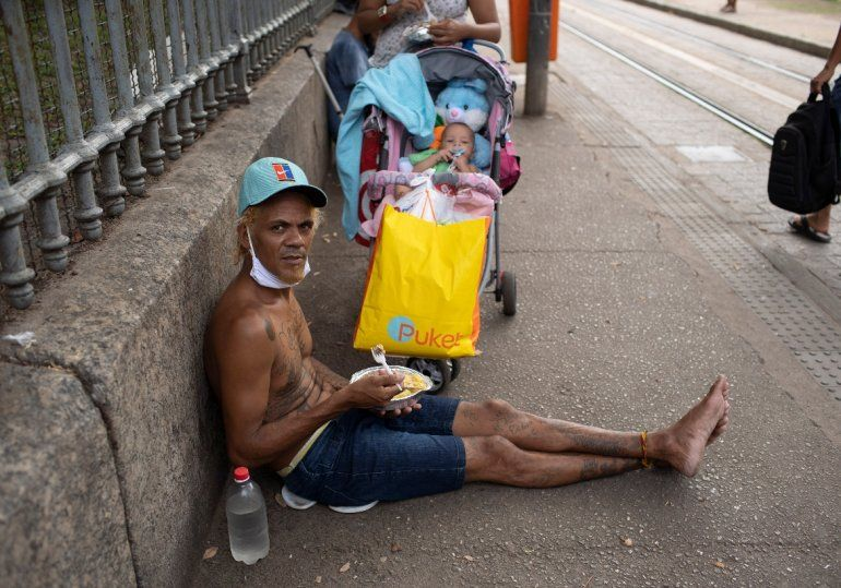 Un hombre mira a la cámara mientras come el almuerzo donado por la Fundación Leao XIII durante la pandemia de COVID-19