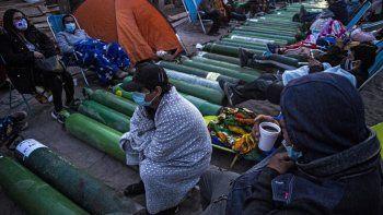 Personas acampan mientras esperan para rellenar cilindros de oxígeno vacíos en Villa El Salvador, en las afueras del sur de Lima, el 25 de febrero de 2021, en medio de la pandemia del coronavirus COVID-19. Los familiares de los pacientes con COVID-19 están desesperados por oxígeno para mantener con vida a sus seres queridos durante una feroz segunda ola de la pandemia en Perú.