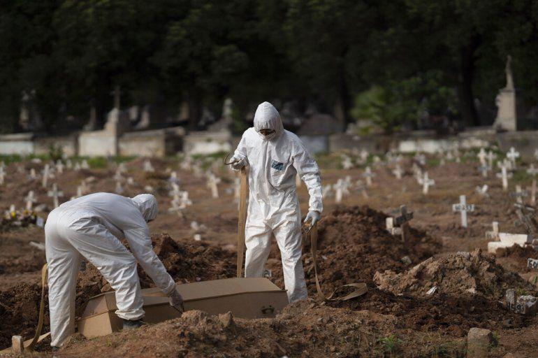 Trabajadores de un cementerio con trajes de protección colocan el ataúd de Paulo Jose da Silva
