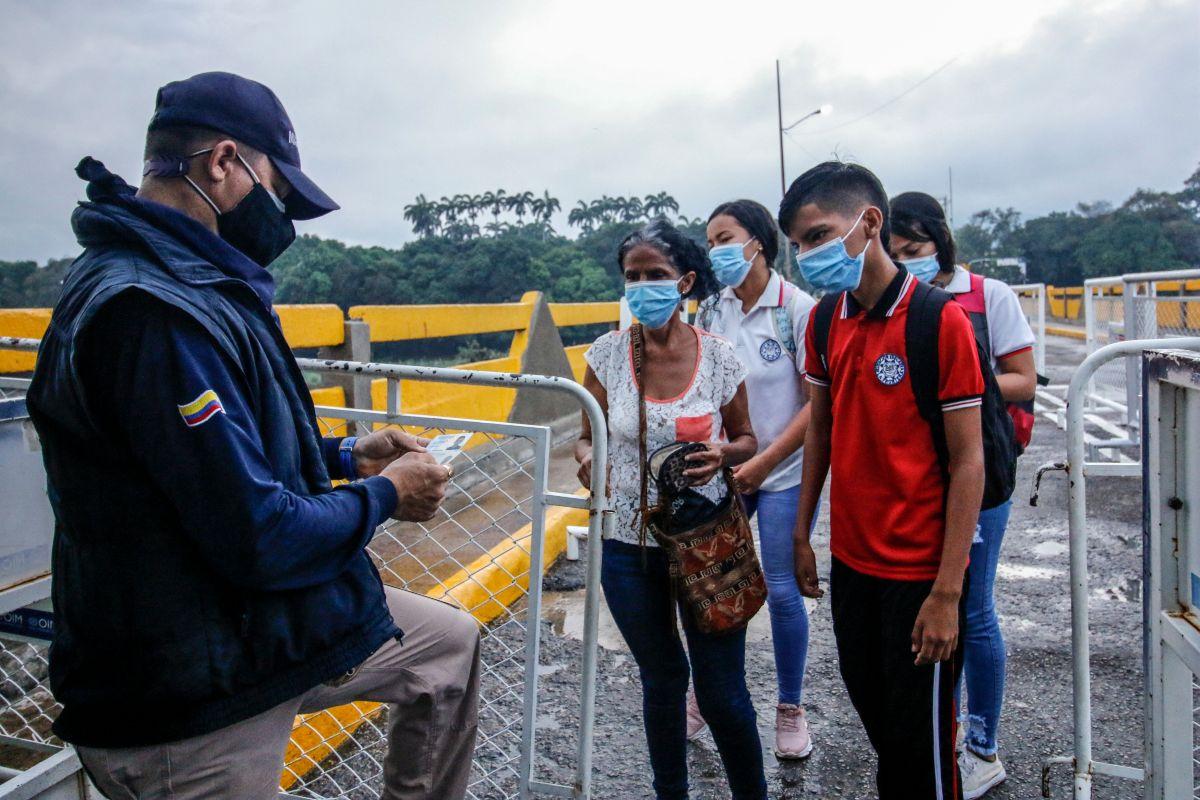 Funcionario de migración colombiano verifica documentos de estudiantes venezolanos luego de cruzar el Puente Internacional Simón Bolívar desde Venezuela a Cúcuta, Colombia.