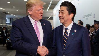 El primer ministro japonés Shinzo Abe (der.) saluda al presidente Donald Trump a su llegada al International Exhibition Center para participar en la Cumbre del G20, en Osaka.