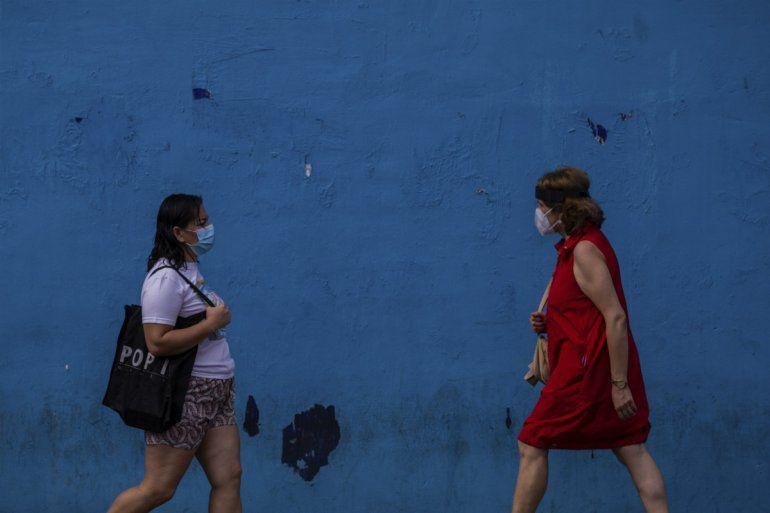 Dos mujeres con mascarillas protectoras contra el coronavirus caminan por el barrio de Vallecas