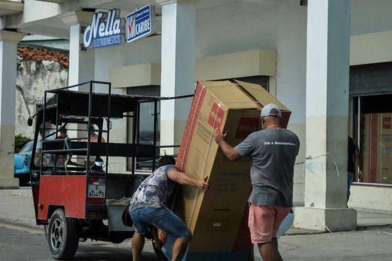 Dos hombres cargan un refrigerador luego de comprarlo en una tienda de La Habana
