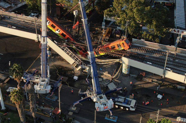 Vista aérea de vagones del metro colgando desde una sección elevada colapsada en la Ciudad de México