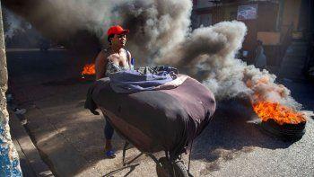 Una mujer aleja su mercancía de neumáticos incendiados por manifestantes durante una huelga nacional que exige la dimisión del presidente haitiano Jovenel Moise en Puerto Príncipe, Haití, el lunes 1 de febrero de 2021.