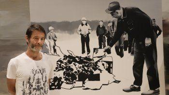 El artista polaco Wilhelm Sasnal posa frente a una de sus obras en una nueva exposición en el Museo Polin de Historia Judía Polaca que confronta la persistente y melancólica presencia del Holocausto en Polonia, el martes 15 de junio de 2021 en Varsovia. La muestra Wilhem Sasnal: Tal paisaje se inauguró este jueves, 17 de junio de 2021.