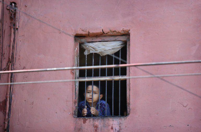 Un niño mira por la ventana de su casa en el barrio viejo de Nueva Delhi