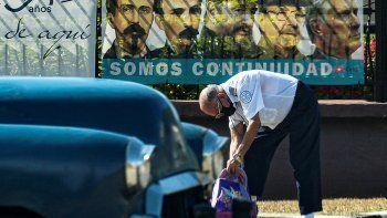 Un hombre chequea un bolso mientras detrás se observa una valla publicitaria con las imágenes de dirigentes políticos históricos junto al actual gobernante Miguel Díaz Canel.