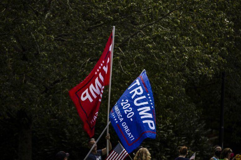 Simpatizantes por Trump sacan banderas este domingo mientras él se dirige a su club de golf