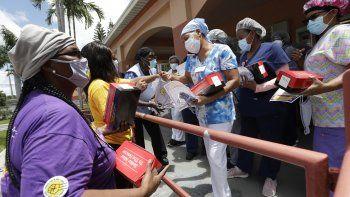 Trabajadores entreganmascarillas para prevenir el contagio del coronavirus en la residencia y centro de rehabilitación de ancianos Franco en Miami, 20 de julio de 2020.