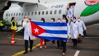 En esta foto de archivo tomada el 26 de junio de 2020, el médico jefe Abel Roberto Fuentes Santiesteban (izq.) Sostiene una bandera cubana cuando llega con una delegación de médicos cubanos al aeropuerto Martinica-Aime-Cesaire en Le Lamentin, cerca de Fort- de-France, en la isla caribeña francesa de Martinica, como parte de un programa de asistencia médica en medio de la pandemia de COVID-19 causada por el nuevo coronavirus.