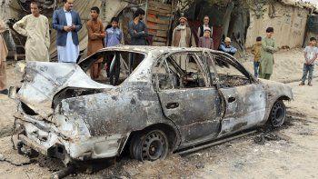 Gente mirando un vehículo dañado por un ataque con un cohete en Kabul, Afganistán, el lunes 30 de agosto de 2021. Varios cohetes golpearon un vecindario cerca del aeropuerto internacional de Kabul durante la retirada de Estados Unidos.