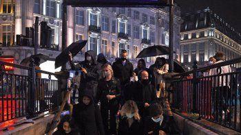 Un grupo de personas ingresa a la estación de metro Oxford Circus en Londres, el viernes 2 de octubre de 2020, después del toque de queda de las 10:00 de la noche que deben acatar bares y restaurantes a fin de frenar un incremento de casos de coronavirus en Inglaterra.