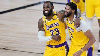 LeBron James (23) y Anthony Davis (3) de los Lakers de Los Ángeles celebran tras la victoria ante los Nuggets de Denver, el lunes 10 de agosto de 2020, en Lake Buena Vista, Florida, durante la temporada de la NBA.